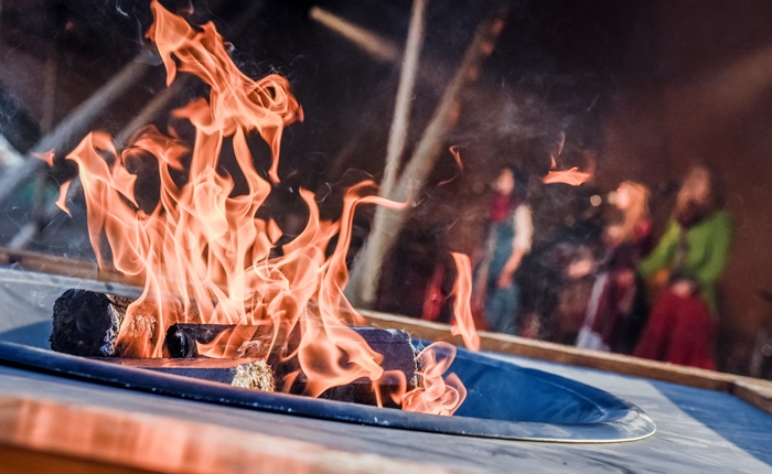 A fire burning in front of a band playing on stage at the Hanse Festival